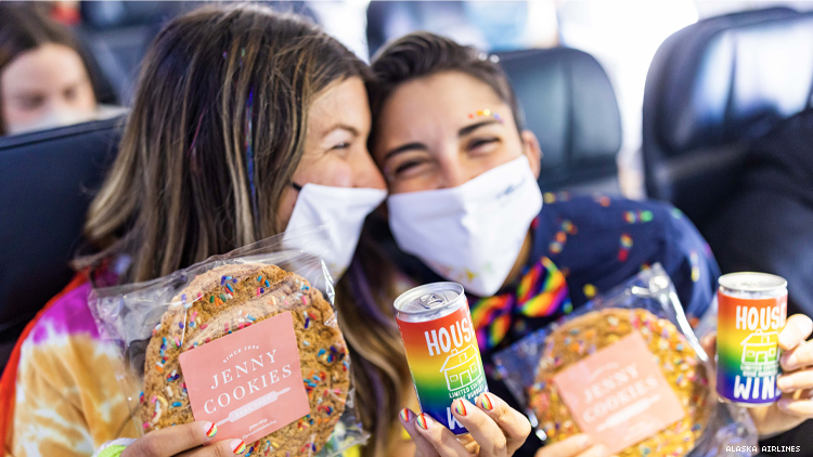 lesbian couple on pride plane showing off their cookies and wine