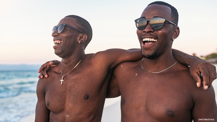 2 Black men with arms around each other's shoulders on a beach