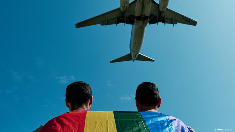 Airplane flies over a queer couple draped in a rainbow flag