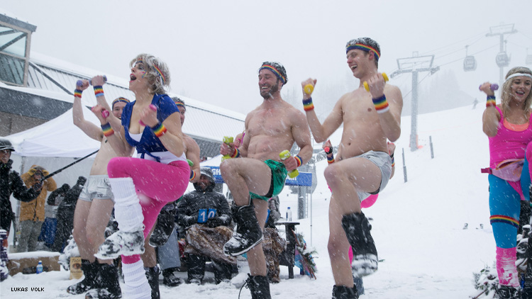 A group in shorts and ski boots exercising in the snow