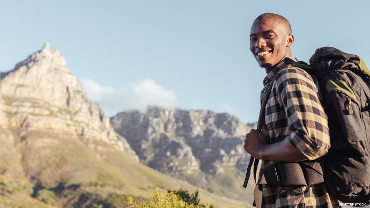 A smiling Black man hiking with mountains behind