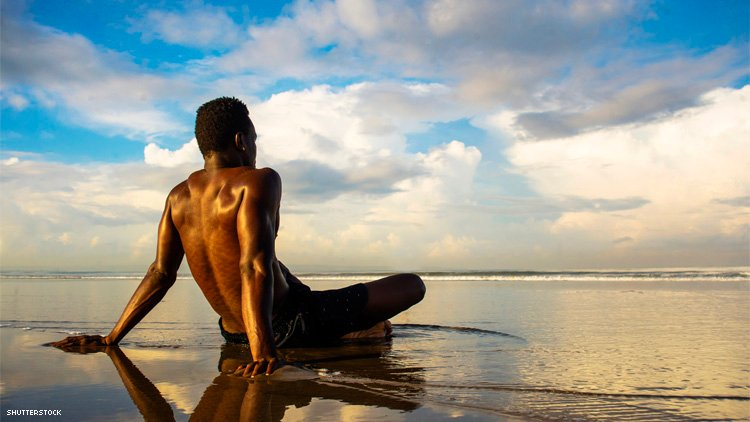 Black man sitting in water on beach
