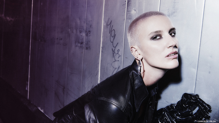 Image of FELIN, pop star with shaved head wearing black leather jacket