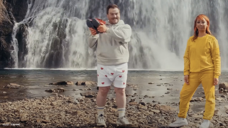 Man in boxer shorts holds aloft sweatpant boots next to rapper Cell7 both in front of an Icelandic waterfall