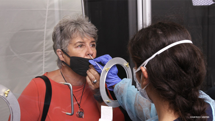 A woman gets and instant COVID test from a United Airlines employee behind glass