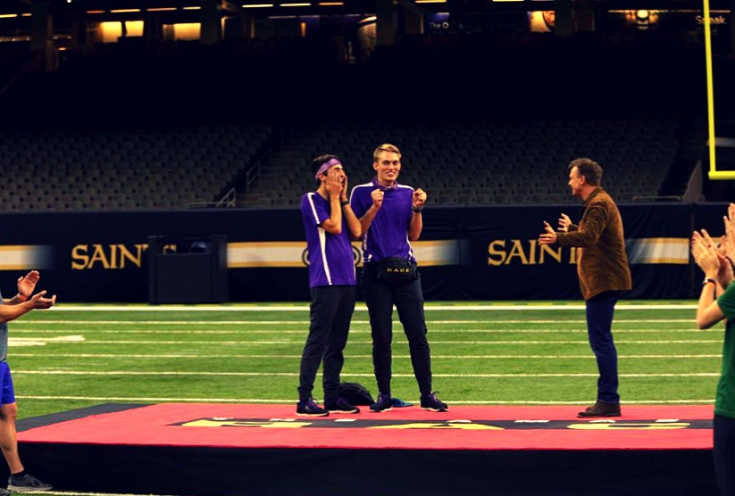 two white men, will and james, look anticipatory at a stadium during amazing race finale