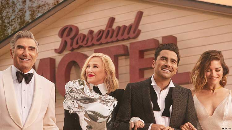 The cast of Schitt's Creek in front of the Rosebud Motel