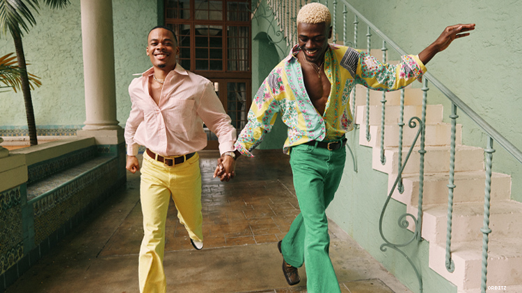 A colorfully dress black gay couple run hand-in-hand