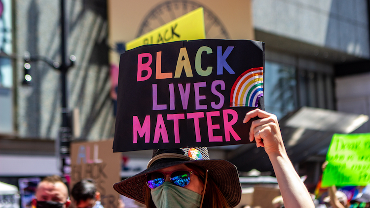 protester holding a sign that says Black Lives Matter