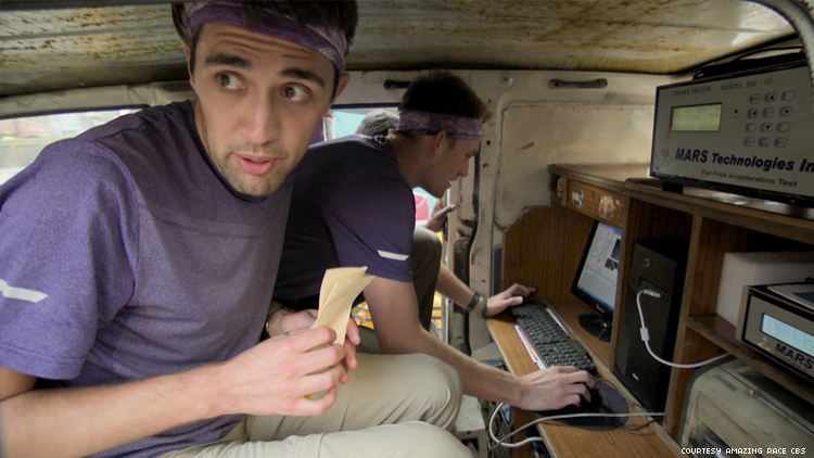 Will and James of 32nd The Amazing Race doing smog tests in a tiny van in India