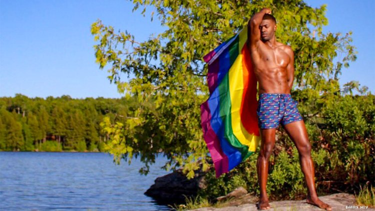 Teraj on edge of lake, in boxers and with a rainbow flag
