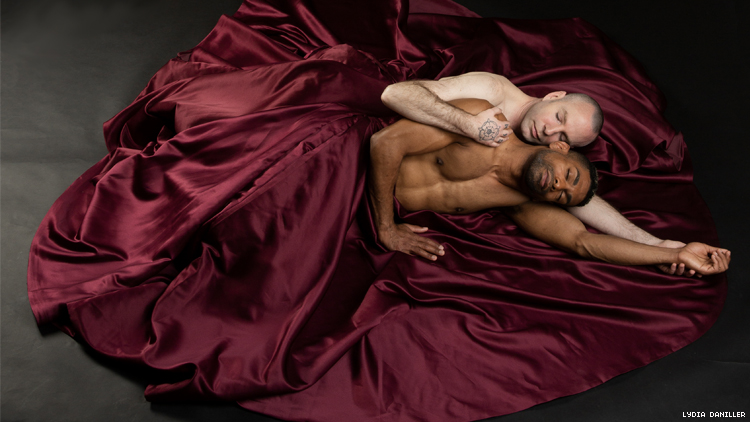 A white and a Black male dancer lie shirtless embracing amid the folds of a oversized purple skirt