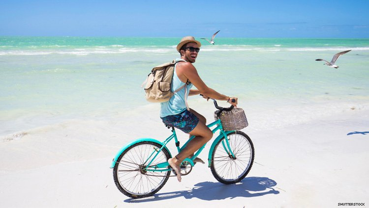 Man on a bicycle on a beach in Mexico