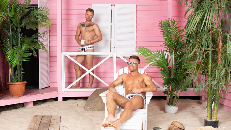 2 gay men in swimsuits in front of pink beach house