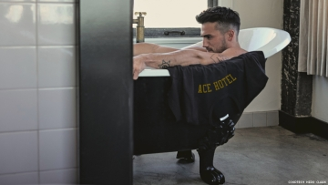 Man in bathtub at Ace Hotel with an Ace branded t-shirt