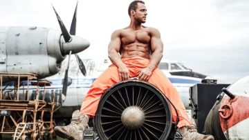 Shirtless man sits on a plane's engine with airplane behind him