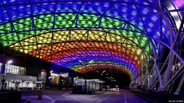 The Atlanta airport at night lit up in rainbow colors to celebrate 50 years of LGBTQ Pride