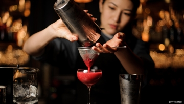 Asian woman bartender with cocktail
