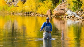 Black man fly fishing in the Rocky Mountains