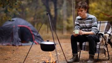 Male Camper Sits by Cooking Fire