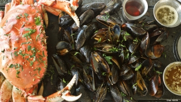 a platter with cooked crab and mussels