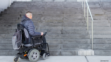 Disabled man using wheelchair, at bottom of flight of stairs