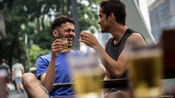 Two gay men of color toast at an outdoor bar