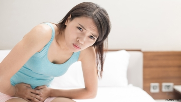 Asian woman suffering from period cramps
