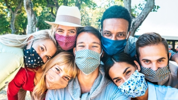group of multicultural friends wearing masks taking a selfie