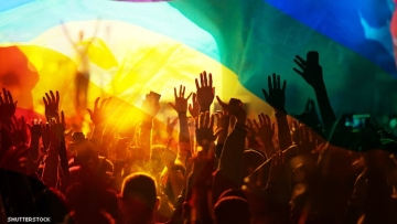 Photo of a group of people with their hands in the air overset with LGBTQ rainbow flag