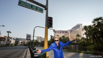 Siegfried stands below the newly named Siegfried & Roy Drive sign