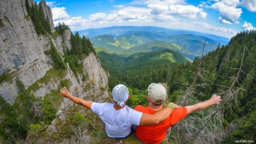 two-young-men-sitting-on-a-cliff-edge-in-the-ceahlau-mountains-in-romania
