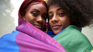 Two Black Lesbians in a Pride Flag