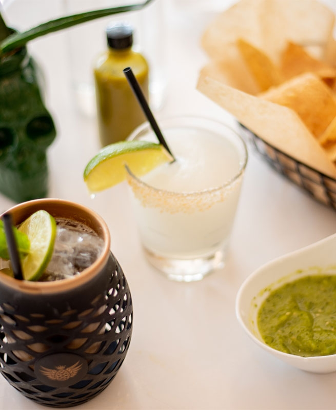 A Margarita next to chips and green salsa