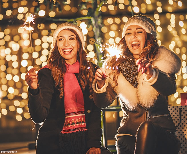 Two women in winter clothing holding sparklers