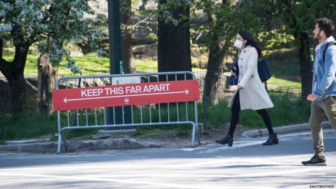 A woman in mask and man without walk past a sign about social distancing in a park