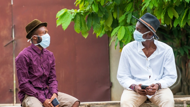 Two young Black men sitting social distance apart with masks on outside