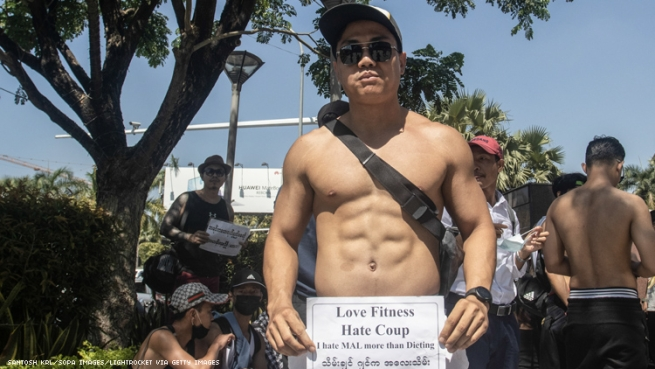 Shirtless man holds sign Love Fitness: Hate Coup in Myanmar