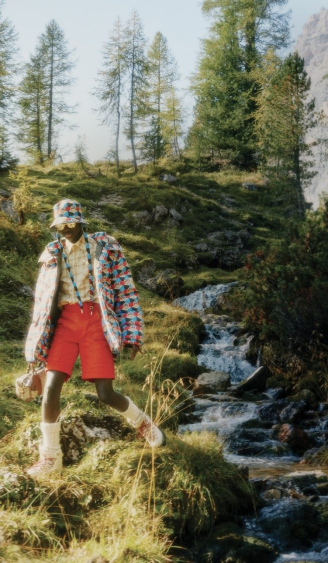 Black model wearing North Face x Gucci outfit next to stream
