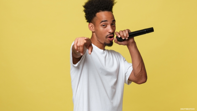 A young Black man singing into microphone isolated on yellow background