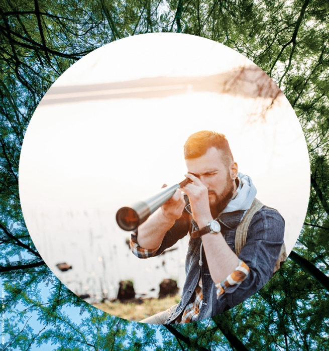 Man using telescope in front of lake