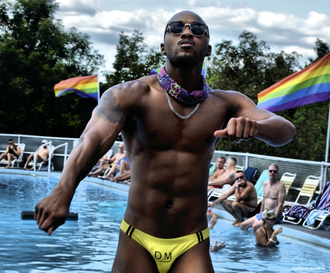 Black man dances in front of pool party
