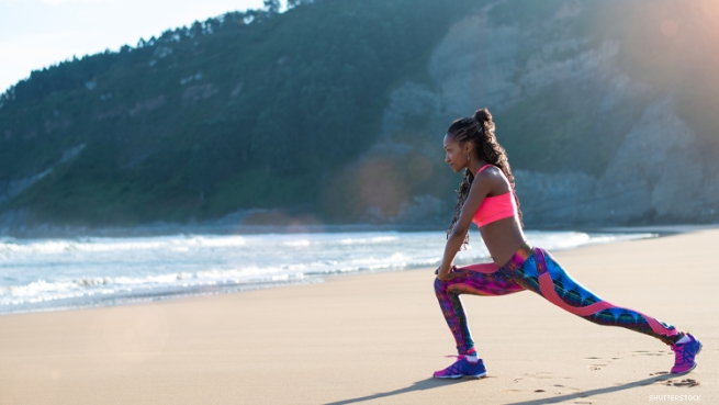 black woman lunging on the beach