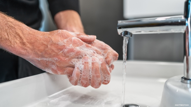 mans hands washing under faucet