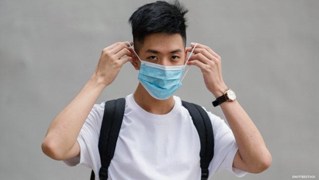 Young Asian man puts on a mask