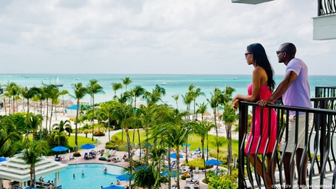 Black couple looking out at Aruba ocean view