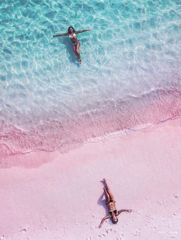 Two women in the blue water and pink sands Komodo Island