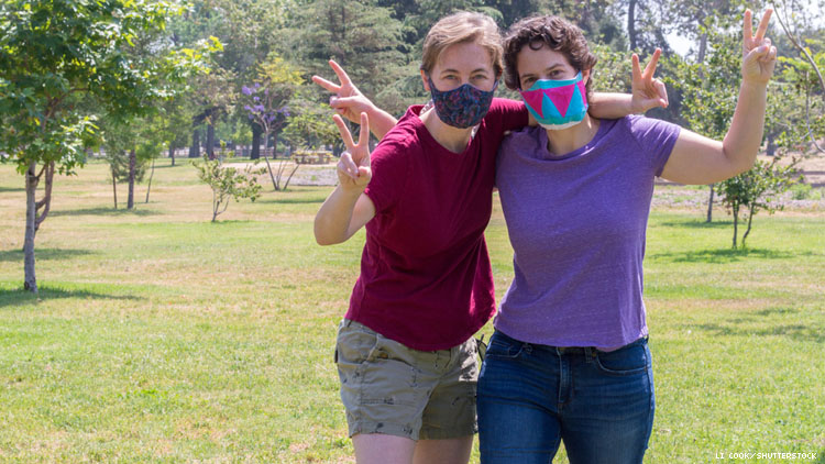 Lesbian couple wearing masks in a park with trees