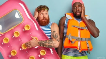 Mixed race gay couple summer clothes, one with life jacket other a pool float, they look nervous