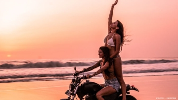 Lesbian couple on motorcycle at sunset on a Bali beach